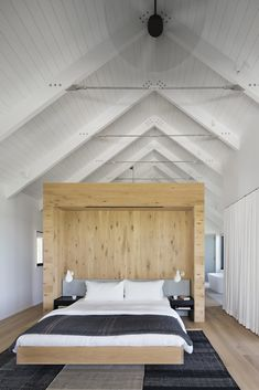 Bedroom, Night Stands, Light Hardwood Floor, Wall Lighting, Rug Floor, and Bed The master bedroom features vaulted ceilings and a light-wood wall to break up the space.     Photo 9 of 18 in Two Cedar-Clad Structures Form a Unique Montauk Retreat