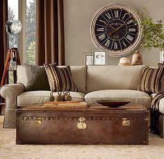 Neutrals...living space...khaki sofa...brown trunk coffee table...striped soft pillows...clock.