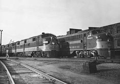 Two generations of E-unit passenger diesels stand at Memphis, Tenn., in August 1952. Illinois Central 4000 (at left) is a 2,000 h.p. E7, while Frisco 2022 is a 2,250 E8. Frisco named its E units after famous horses; 2022 is Champion.  James G. La Vake photo