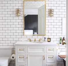 Bathroom - white subway tile with black grout, brass hardware. Domino Magazine