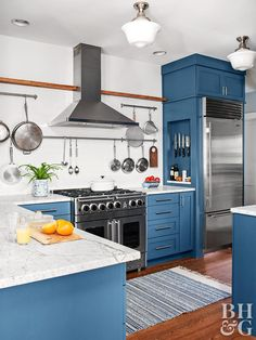 These gorgeous kitchen trends—including minimal upper cabinetry, sparkling quartz counters, and one-of-a-kind ceiling treatments—are guaranteed to stand the test of time. Blue kitchen with nook beside fridge for storing knives. Blue Kitchen Cabinets, Blue Kitchen Decor, All White Kitchen, Upper Cabinets, Kitchen Colors, New Kitchen, Kitchen Ideas, Dark Cabinets, Kitchen Island
