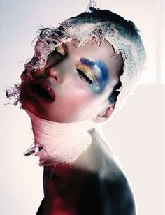 """Beauty"" editorial - ""This stunning beauty editorial uses blue and yellow shades of eye shadow and some head bandaging to create a look that says battered beauty. The why is unclear, but the result is actually quite beautiful."""