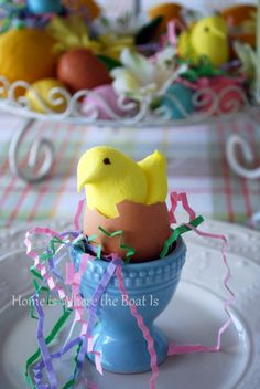 Peeps in broken egg shells nestled in an egg cup in colored paper grass. By Mary @ http://homeiswheretheboatis.wordpress.com/2012/03/22/garnish-with-easter-peeps/#