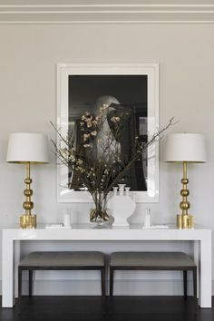 How about this living room decorating idea? A low console table with two table lamps in gold powder and two benches beneath the console! Lovely.