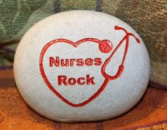 Rock painted white a heart inside the heart the words nurses rock on the side apart step a scope