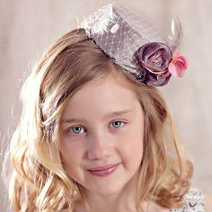 his darling mini pill box hat is perfect for that special holiday outfit. Silver-grey silk covers this handmade pill box frame with accents of dusty pink silk rosettes, vintage pink flowers, grey feathers and lovely pink dot veiling .  This darling hat comes with hat elastic.