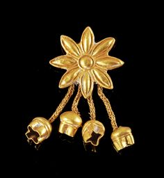 Ancient Greek gold fibula in the form of a flower with dangling pomegranate pendants, dated to the 7th century BCE. Image found on Pinterest, but no other source was given.