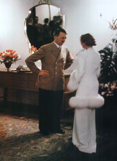 Adolf Hitler converses with a beautifully dressed young German woman.
