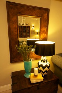 #WatchandPin  Mirror with wooden frame, side trunk with a teal vase sitting next to a black and white table lamp.  #DearGenevieve makeover (Air Date:  Sept 21 4:30pmEST)