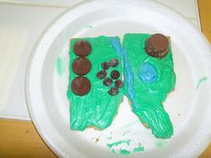 Edible island with landform features  (Graham cracker forms shape, ice w/ blue & green; Reese's cups for plateaus, Kisses for mountains)