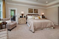 Master bedroom with high tray ceilings, a sitting area and a neutral color palette.
