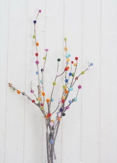 Poms poms aren't exactly traditional, but they certainly create a festive tree when attached to rustic branches and arranged inside of a simple glass vase. See more at Style Carrot »