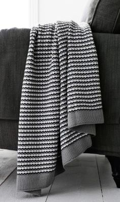 A black, white and grey throw rug hung over a grey chair.