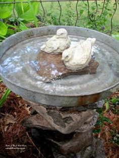 DIY Stacked Stone Bird Bath; stacked stones (glued together) holding up a slightly rustic silver tin bath with extra falt stones inside to hold up the sweet stone birds. Suprisingly easy!