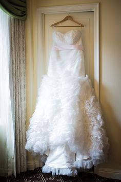 Beautiful ruffled train on this corset wedding dress.  Perfect for spring, with poofy vintage style.  The gorgeous blush pink sash makes this gown a fairy tale dream come true!  Would be beautiful for a pastel, or beach wedding with it's lace accented bodice.  Available in any size, including plus size, from Bridal design house Avail & Company.