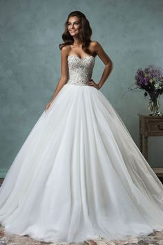 Elegant wedding dress accenting brilliant beaded on the strapless sweetheart bodice matches ball gown tulle skirt. Low back.