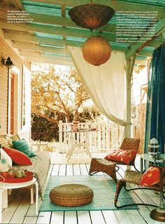 Elements such as the pergola, drapery, seating, and decor turn a bare deck into an outdoor living space.