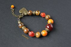 Red jasper bracelet Carnelian stone Tiger eye stones bracelet Boho style Brown stones bracelet Orange jade Heart pendant bracelet Carnelian   Womens bracelet with brown stones. This bracelet includes natural stones: red jasper, tiger eye round beads, a large bowl of carnelian, orange jade. Bracelet supplemented antique bronze fittings and pendant heart.   Size is 6'5 inches (16 cm) and has a lobster claw clasp that can be attached to other links in the chain, making the bracelet adjustable…