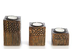 Carved with a pebble motif and wavy lines, these three mango-wood tea light holders will add an organic texture to a room.