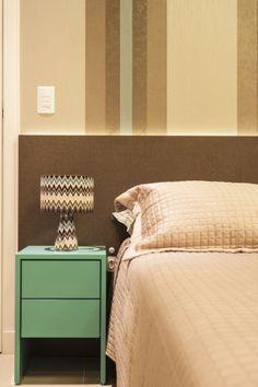 Ao lado da cama, o criado mudo se destaca pela cor da laca que oferece certo frescor à decoração.
