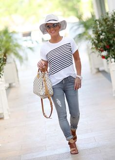 Fashionable summer travel look with simple statement tee and jeans. Add a necklace to elevate the look. Summer fashion over 40 | 40 Plus summer fashion | Summer outfit ideas