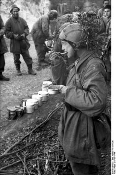 Italian Fascist R.S.I soldiers and German paratroopers eating together.  Monte Cassino, Italy, 1943.