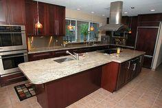 Dark oak cabinets with a big island and granite countertops