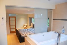 Image 12 of 15 from gallery of Smart Open-Concept Bathroom: Ideas for Balancing Privacy with Openness. Open concept design of contemporary bathroom in bathroom with frosted sliding glass screen door by portal design inc Room Partition Wall, Room Partitions, Glass Screen Door, Portal Design, Bedroom With Bath, Master Bath, Master Bedroom, Bathtub Remodel, White Oak Floors