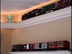 "O scale model train shelf layout.  This is an updated video to show the following additions to my layout:     - added rope lighting behind the track  - added scale neon signs in the four corners  - upgraded the train to a smoother, larger one, with sound  - added ""display"" shelving for my extra train and cars  - connected all the controls to a w..."