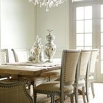 Chic modern French dining room design with rustic wood trestle dining table, gray French Oly Studio Sarah dining chairs upholstered in tan linen with nailhead trim, mercury glass vases and canisters, French doors and transom windows.