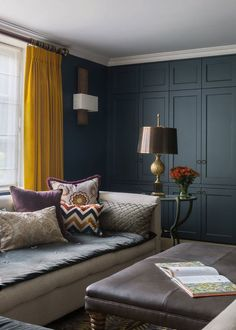 Dark blue panelling contrasts with mustard yellow curtains in a traditional country living room #livingroomdesignscasual