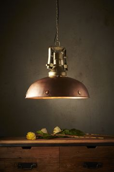 A warm copper dome with portholes along the rim supported by a chunky industrial fitting and chain in brass.  This pendant strikes a perfect balance between its industrial feel, colour and curved form.