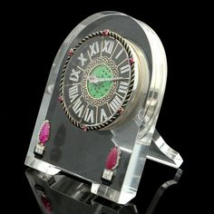 AN ART DECO ROCK CRYSTAL, DIAMOND AND ENAMEL GEM-SET STRUT CLOCK BY CARTIER c.1929  A fantastic arch-shape desk clock in the art deco style carved from rock crystal with a gold and black enamel dial with rose-cut diamond Roman numerals, the diamond hands set against a carved and pierced jade central plaque, the striped black enamel surround with six sugar loaf ruby highlights, the front with two applied carved ruby trees with diamond and black enamel planters, the reverse signed Cartier and…