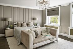 Bespoke headboard, upholstered wall in this luxurious master bedroom. Seating area, sofa at foot of bed, stunning modern chandelier ceiling light, bedsides with storage. Roman blinds in Georgian sash windows, textured wallpaper. Townhouse in Knightsbridge