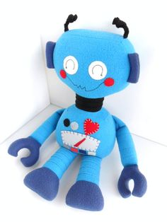 This adorable robot ragdoll is made from turquoise blue fleece with navy blue and black accents. The robot is adorned with a hand-appliqued gauge