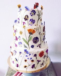a pure white wedding cake all decorated with edible blooms looks wild and very chic