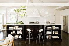 white kitchen, black island with low bookcases, mod stools
