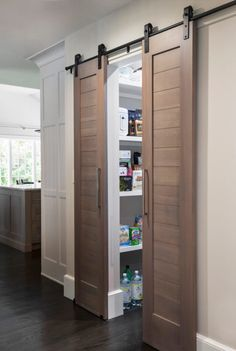 Idea for Pantry door; one panel is blackboard Walnut stained shiplap dual pantry doors on rails open to reveal a kitchen pantry. Rustic Pantry Door, Kitchen Pantry Doors, Sliding Pantry Doors, Closet Doors, Kitchen Pantries, Kitchens, Room Doors, Stained Shiplap, Pantry Design