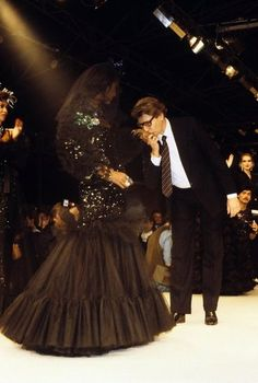 Yves Saint Laurent: Yves Saint Laurent on the catwalk with a model during his Spring 1985 Haute Couture show in Paris in January 1985.
