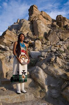 Traditional Hopi girl, Povi Lomayauma 16 year old teenager, dressed in traditionally woven cotton dress holds a woven wicker plaque stands on an ancient staircase leading to the town of Tewa The stone steps are located on the First Mesa near Polacca Arizona