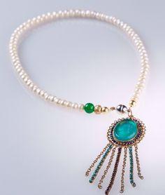 Nostalgischer Glamour: Stilvoll legt sich die Kette aus schneeweißen Süßwasser-Perlen auf das Dekolleté ihrer Besitzerin. Kombiniert mit goldenen Schmuckelementen, einer grünen, Glück verheißenden Jade-Perle und einem Kamee-Anhänger aus Glas verbreitet sie köngliches Flair.Süßwasser-Perlen in Weiß mit einer grünen Jade-Perle und einem grünen Kameeanhänger, der mit magentafarbenen Glas-Steinen eingefasst ist.Länge: 42 cm