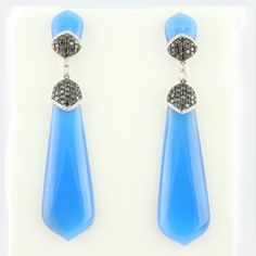 Blue Agate & Diamond Earrings Blue agate dangle earrings with petal like small top, a single row of round brilliant diamonds, a cluster of black diamonds, and a longer shaped blue agate. 4: blue agates, .20ctw round brilliant diamonds, 1.06ctw black diamonds, 18kt white gold.
