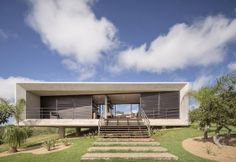 Un prisma compatto in calcestruzzo con ampie vetrate scorrevoli che si aprono sul paesaggio collinare: Casa Solar da Serra è una villa poco fuori Brasilia progettata dallo studio 3.4 Arquitetura