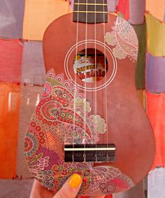 Check out this DIY Fancy Ukulele Make Over on my blog. I used a removable paisley laptop decal from Walmart to cover up the ugly factory art that was on my uke. This is a super easy way to put a personal DIY touch on any instrument.