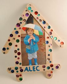 """How You Make House: Arrange craft sticks so that two are parallel and one crosses them about 3/4″ from the bottom. Secure with glue. Arrange last two sticks so they meet in a """"point"""" at the top. Make sure your picture will fit behind house shape and glue at top and sides. Glue sequins to craft sticks and write name using glitter glue."""