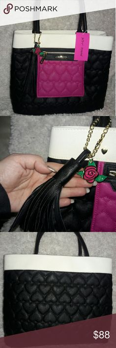 """NWT Betsey Johnson Bag NWT. Large Betsey Johnson bag with signature quilted design. Could be used as a handbag, a carry-all, or a work bag. Black all around with white """"stripe"""" along top. Has pink """"flap"""" on front with a zipper and logo. Includes a cute black tassle and rose Betsey ornamentation. Exterior man-made. Interior has 3 compartments, 2 with magnet closure, 2 slip and 1 zippered pocket. Other is full height zippered compartment. Dimensions are 12"""" H x 15"""" W x 6"""" W, strap drop is 9""""…"""