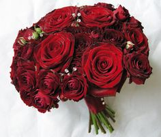 "velvety "" Grand Prix"" roses combined with a deeper red spray rose and sprays of clear crystals. The bouquet is hand tied and the stems finished with a toning ribbon and diamante pins."