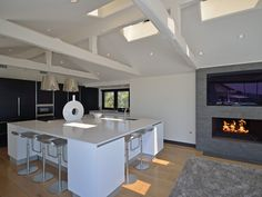 This sleek and modern kitchen features a large island with eat in areas and opens up to the dining room with fireplace. 9332 Nightingale Dr   Bird Streets