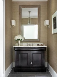 Taupe and black powder room features walls clad in taupe textured wallpaper, Phillip Jeffries ...