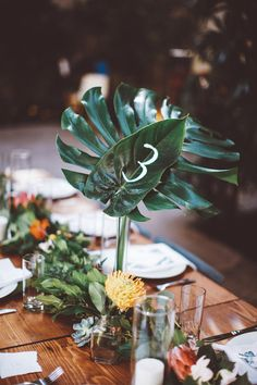 Botanical centerpiece with large leaves used as table numbers | Image by Katie Hoss